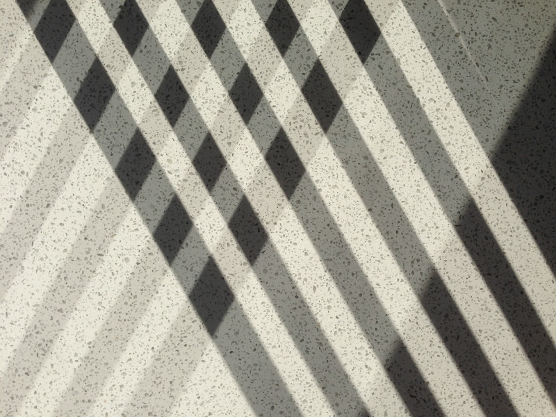 shadows of chair slats on a smooth stone surface