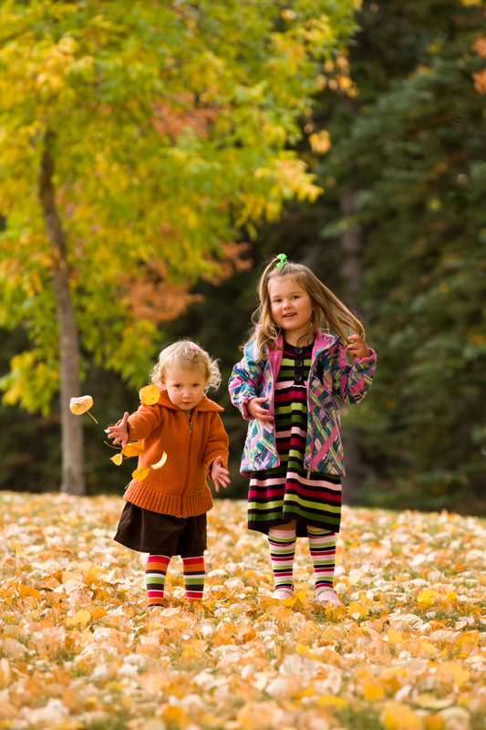 Two young girls dressed for the chill playing with fallen leaves.
